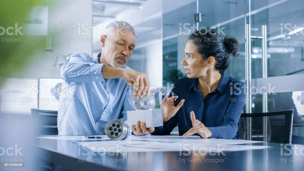 Experienced Male and Female Industrial Engineers have Discussion, Making Adjustment and Perfecting Parts, They Work on a Machinery Component Design. They Office is Stylish and Modern Looking. stock photo
