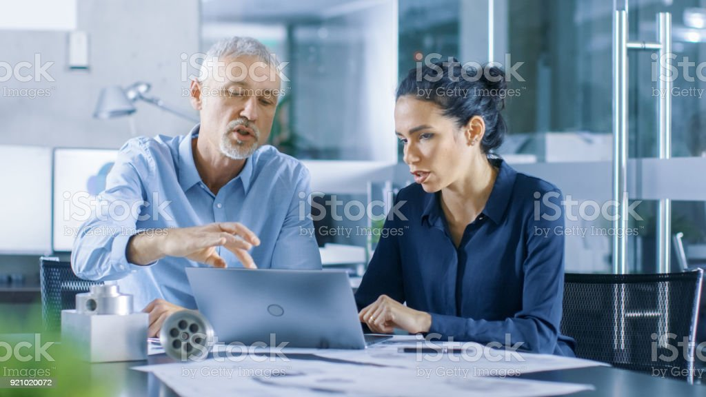 Experienced Male and Female Industrial Engineers have Discussion, Making Adjustment and Perfecting Parts, Type Corrections on a Laptop, They Work on a Machinery Component Design. stock photo
