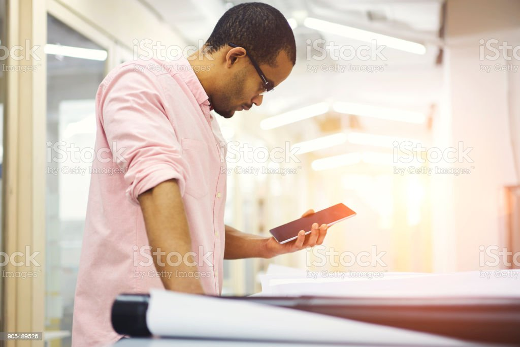 Experienced male architect drafting blueprint of new project using recommendation from engineers and client's requirements saved on special application installed on touchpad connected to 5G wireless stock photo