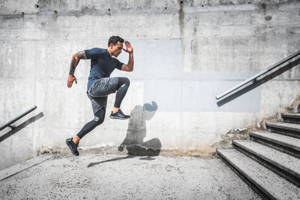 Experienced Male Athlete Running Stairs with High Knees stock photo