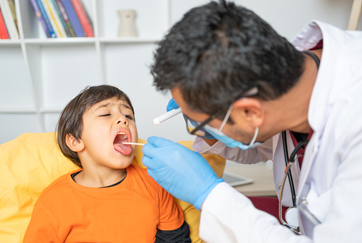 Experienced male pediatrician is examining  little child patient throat using wooden tounge depressor and flashlight in living room while visits at home for health care.