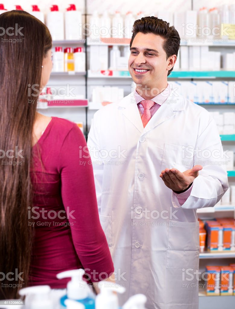 Experienced pharmacist counseling female customer stock photo
