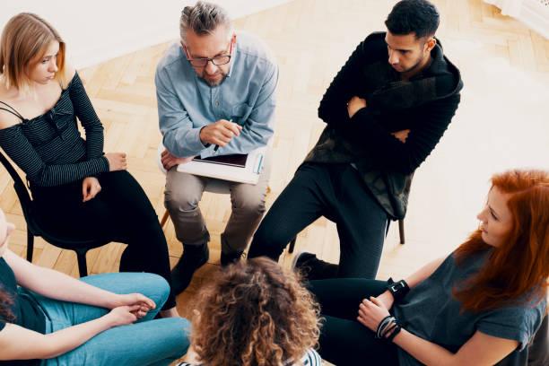 erfahrene psychotherapeut den heilungsprozess, eine frau mit zorn-management-themen zu erklären, während der gruppentherapie-sitzung - anti unordnung stock-fotos und bilder