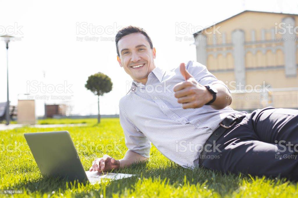 Erfahrene entfernten Arbeiter mit seinem Laptop auf dem Rasen liegend - Lizenzfrei Anwerbung Stock-Foto