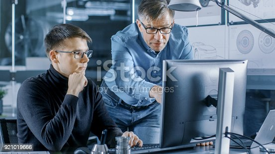 istock Experienced Senior Engineer Consults Young Designer about Project, They Have Discussion and Work on a Personal Computer. 921019666