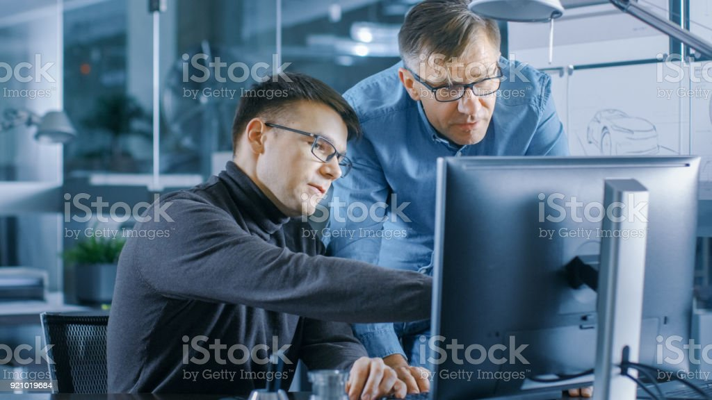 Experienced Senior Engineer Consults Young Designer about Project, They Have Discussion and Work on a Personal Computer. stock photo