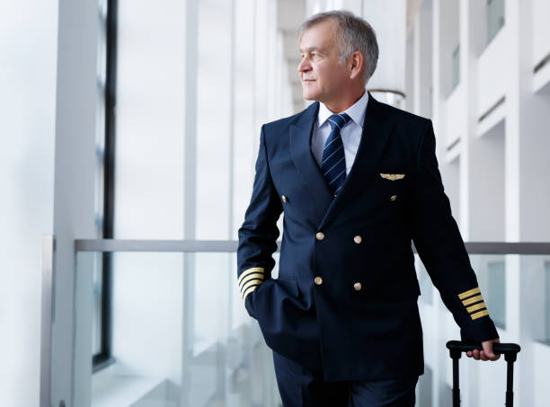 Experienced senior pilot pulling his luggage in the airport terminal Senior Pilot, Captain,  Men, Occupation, Pilot, Airport pilot stock pictures, royalty-free photos & images