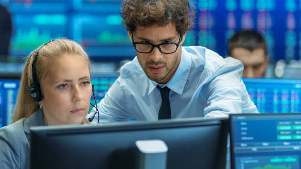 Experienced Stock Exchange Trader Teaches His Apprentice at Her Workstation. Multi-Ethnic Team at Stock Exchange Office is Busy Selling and Buying Stocks on the Market. Displays Show Relevant Data Numbers. stock photo