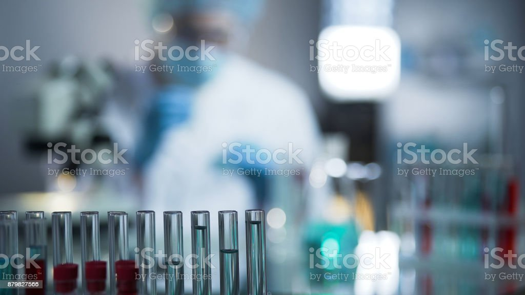 Experienced virologists conducting screening of fluids samples to invent vaccine stock photo