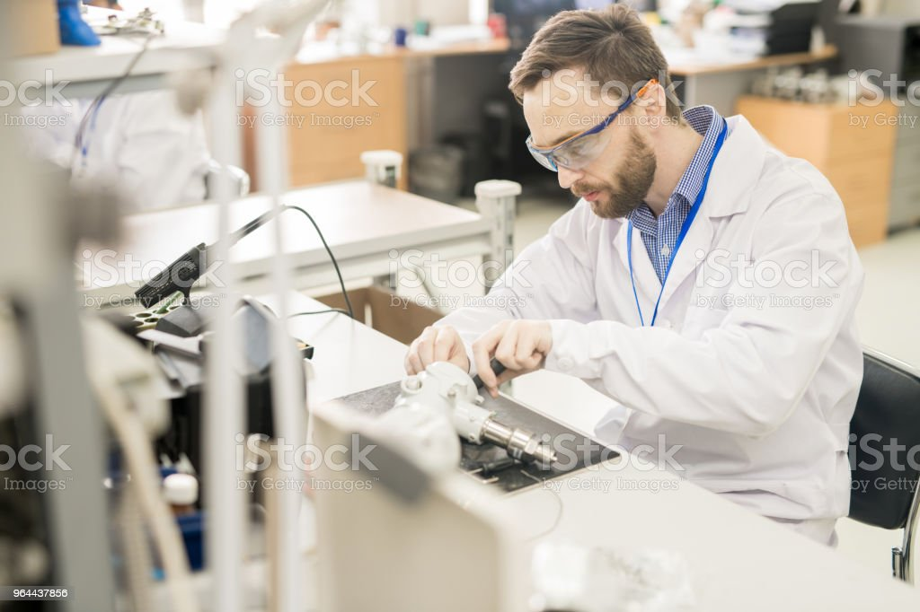 Experienced worker taking measuring device apart - Royalty-free Adjusting Stock Photo
