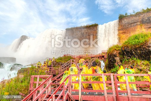 Poncho clad tourists walk on the wooden stairs leading to the Bridal Veil Falls, an offshoot of American Falls, at Niagara Falls between New York, USA, and Ontario, Canada.