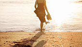 Rear view shot of a woman standing at the beach and splashing water