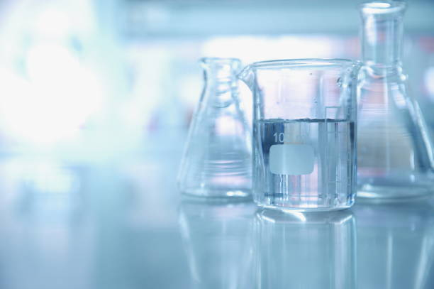 experiment water in beaker and flask in chemistry science laboratory background stock photo