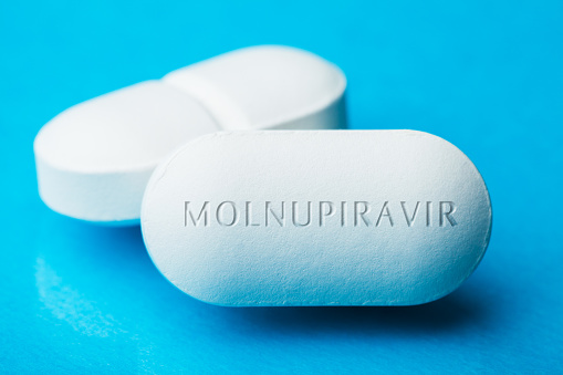 COVID-19 experimental antiviral drug MOLNUPIRAVIR, two white pills with letters engraved on side, potential experimental WHO Coronavirus cure, pandemic outbreak crisis, isolated on blue background