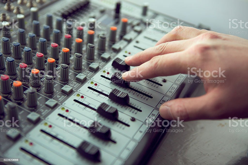 Expert adjusting audio mixing console stock photo