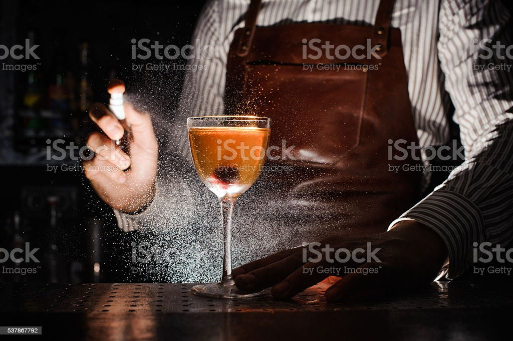 Expert barman is spraying on cocktail stock photo