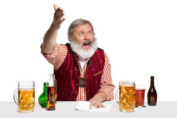 Expert barman with beer at studio The senior expert male barman with beer at studio isolated on white background. International barman day, bar, alcohol, restaurant, beer, party, pub, St. Patrick's Day celebration concept old man working in a pub stock pictures, royalty-free photos & images