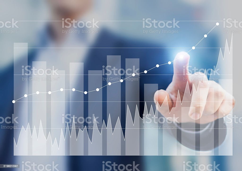 Expert businessman using business intelligence to sketch success on charts stock photo
