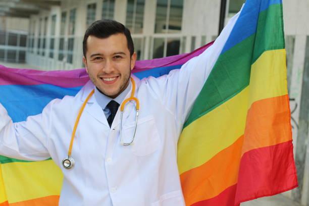 Especialista em saúde gay erguendo a bandeira de arco-íris - foto de acervo
