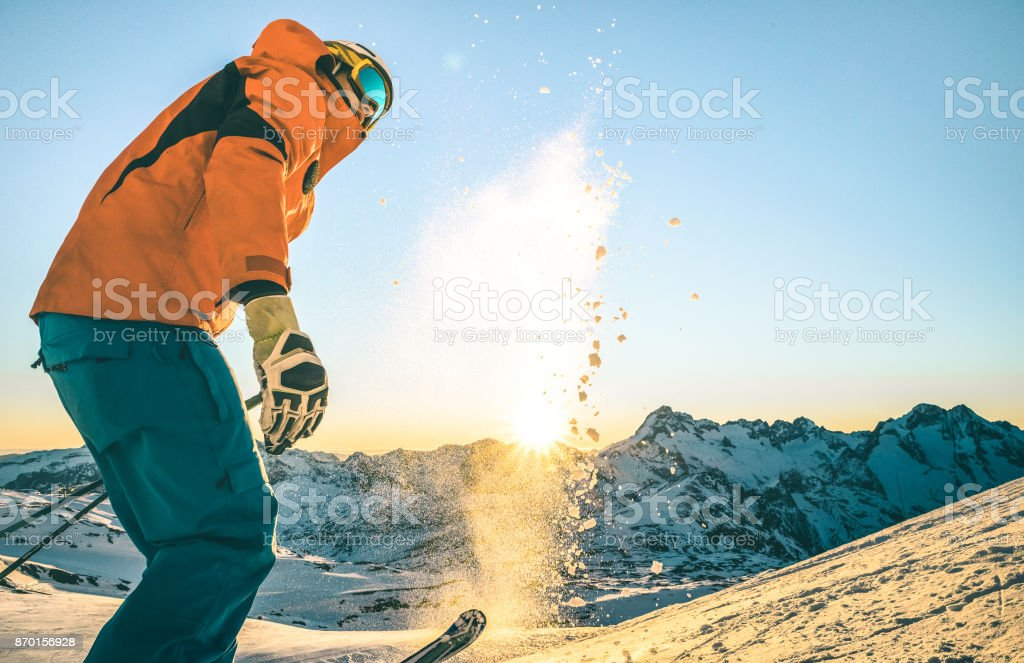 Expert professional skier at sunset on relax moment in french alps ski resort - Winter sport concept with adventure guy on mountain top ready to ride down - Side view point with teal and orange filter stock photo