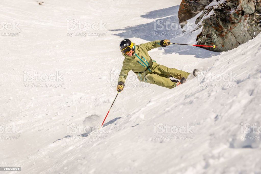 An expert skier in green jacket and ski pants skiing at high speed on...