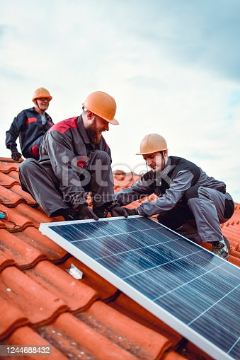 Expert Workers Positioning Solar Panel On House Rooftop