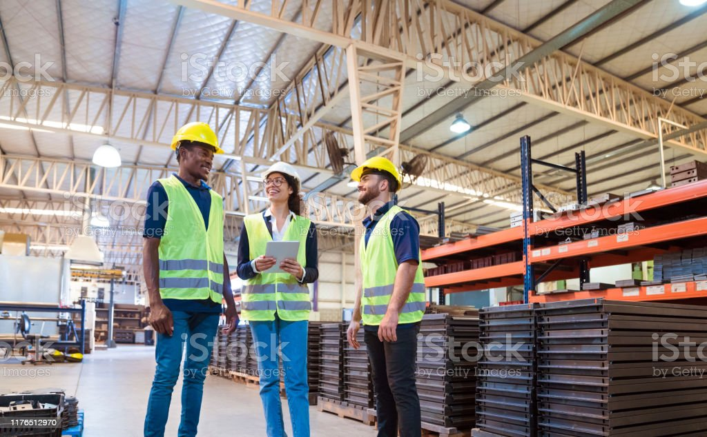 Expertise discussing in manufacturing factory Smiling expertise discussing while standing in industry. Female manager is working production workers. Engineers are related to manufacturing occupation. 20-24 Years Stock Photo