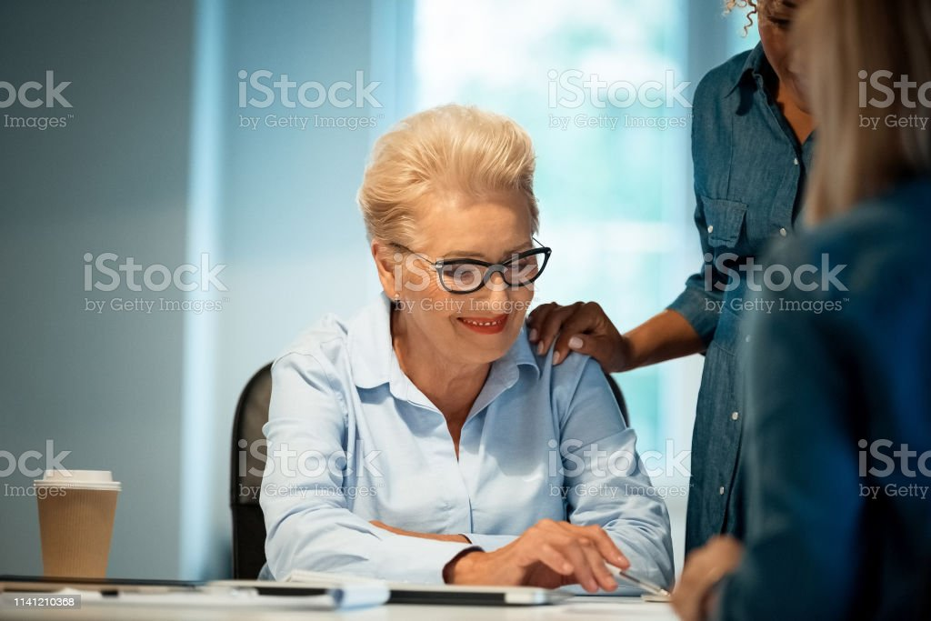 Expertise discussing new plans with businesswomen Smiling elderly expertise discussing plans with businesswomen. Professionals are building new strategy together. They are working in start-up office. 35-39 Years Stock Photo