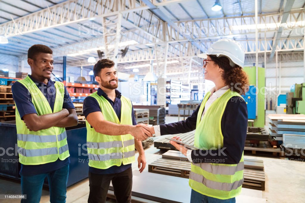 Expertise shaking hand with manager in factory Female inspector shaking hand with worker in factory. Expertise is with arms crossed looking at manager by colleague. They are working in manufacturing company. 20-24 Years Stock Photo
