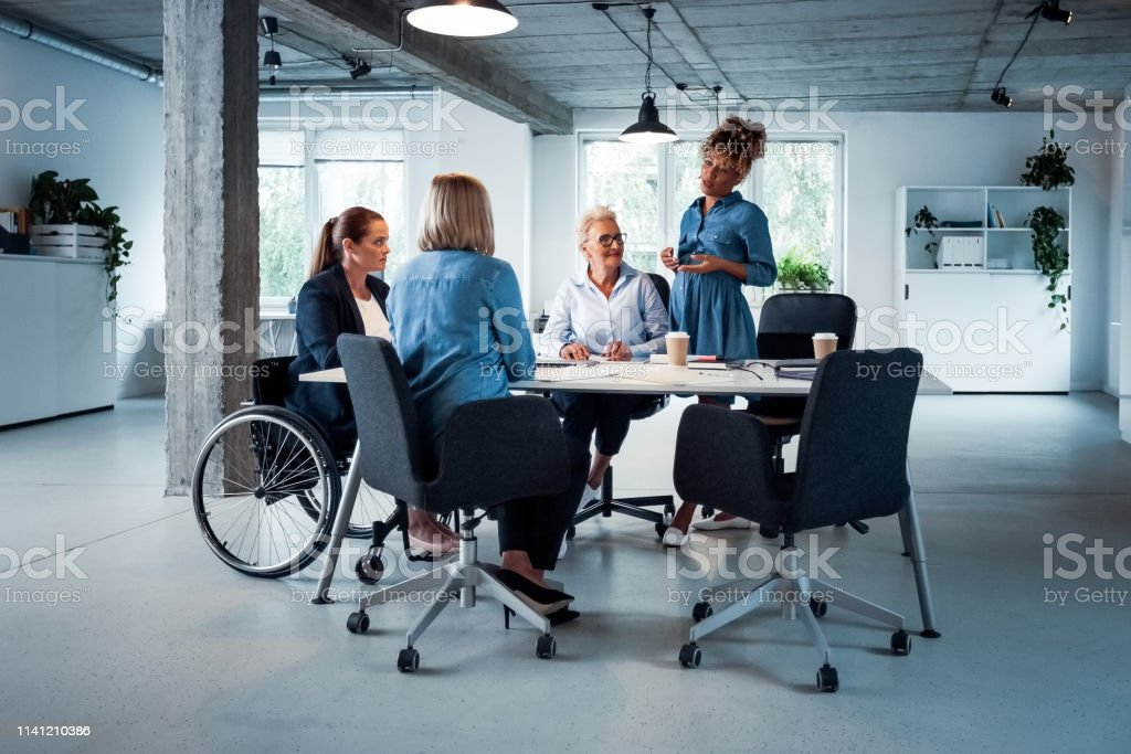 Expertise sharing ideas with colleagues in office Pregnant expertise sharing business ideas with colleagues in office. Confident professionals are brainstorming at desk. They are working together. 35-39 Years Stock Photo