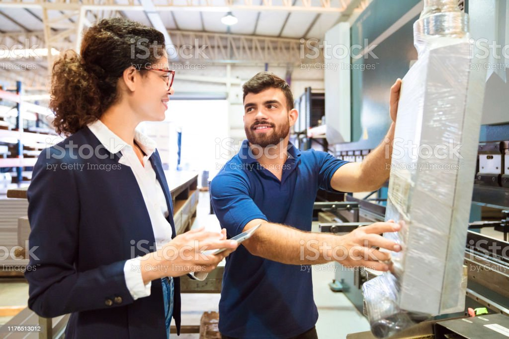 Expertise working in manufacturing industry Expertise working in manufacturing industry. Worker is using machinery while manager holding digital tablet. Smiling colleagues are looking each other. 20-24 Years Stock Photo