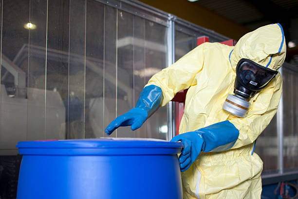 Experts disposing infested material Experts disposing infested material in factory hazardous chemicals stock pictures, royalty-free photos & images