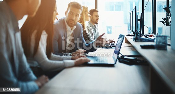 Closeup side view of group of IT experts completing a task in their office. There are three men and two women sitting side by side at a long office desk. Couple further from the camera is in sharp focus.