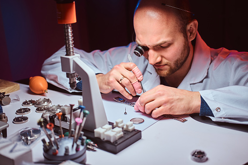 Smart watchmaker is restoring cutomer's watch at his own repairing studio.