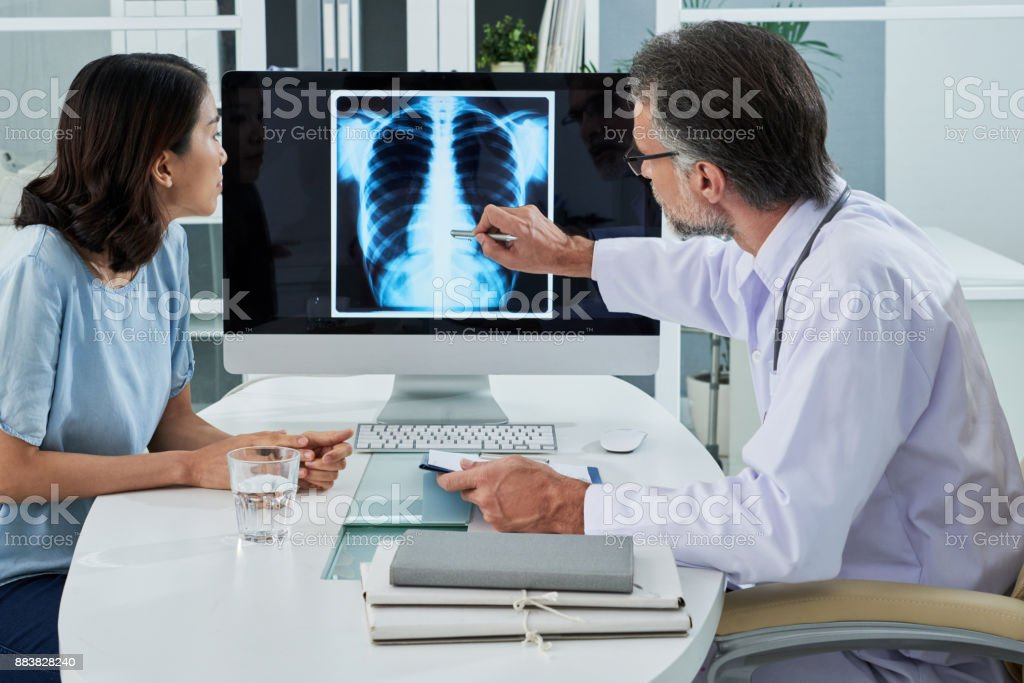 Explaingin x-ray Doctor explaining lungs x-ray on computer screen to young patient X-ray Image Stock Photo