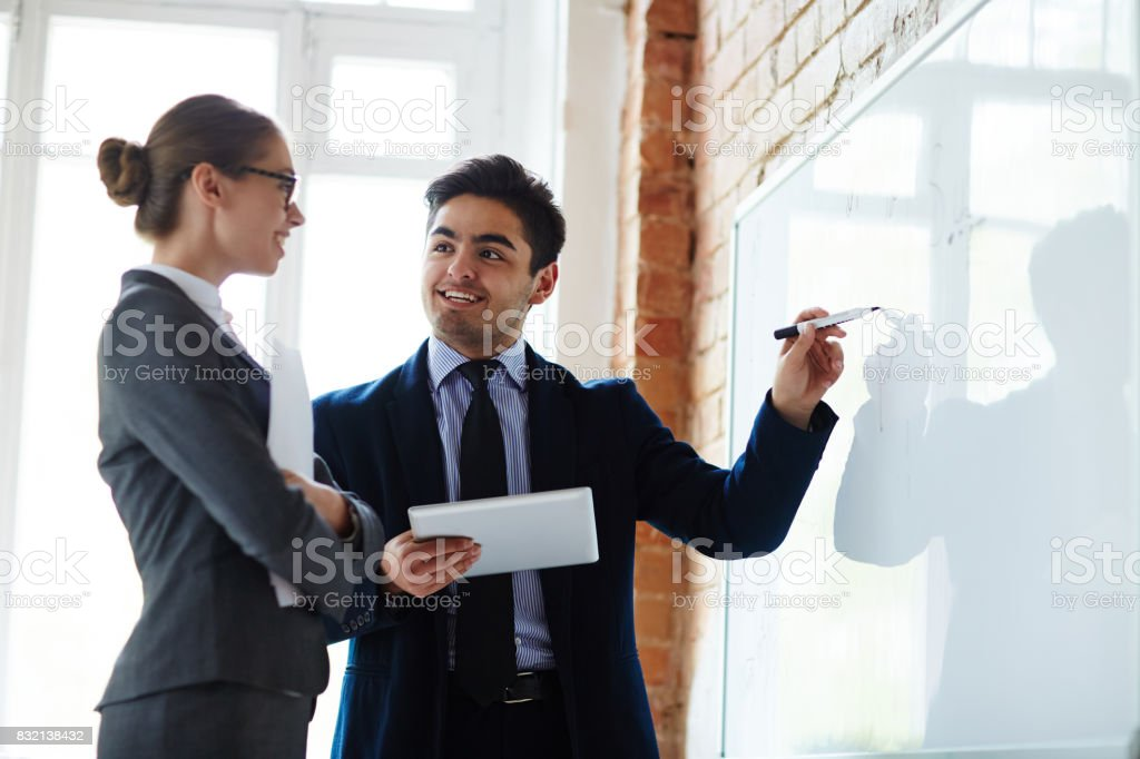 Explaining data on whiteboard стоковое фото