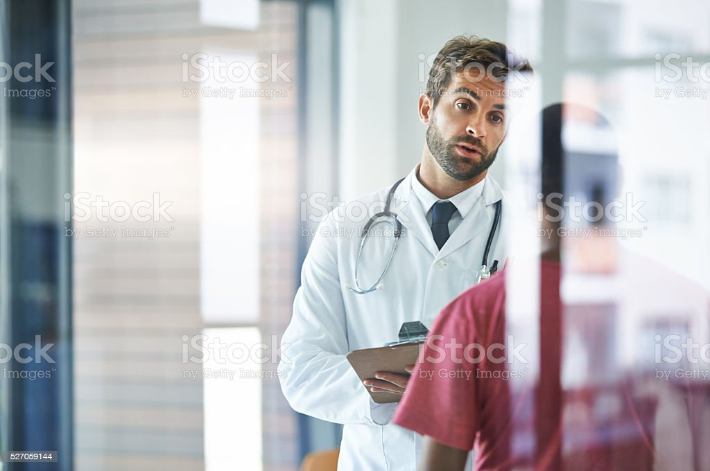 Explaining the situation carefully Shot of a male doctor talking with a patient in a hospital lobby 30-39 Years Stock Photo