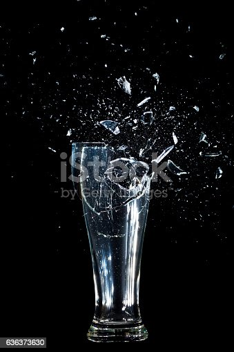 Exploding Glass cup shattering over black background.