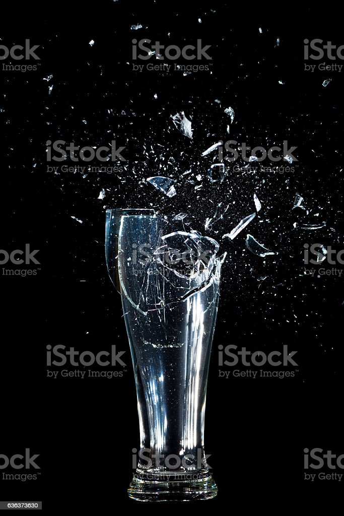 Exploding Glass cup shattering over black background. stock photo