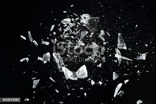 Exploding glass pieces, studio shot, selective focus.