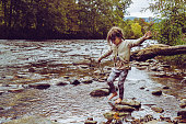 Little child in a river or stream in a rural, wooded area. Beautiful nature and child full of adventure. Barefoot, candid, vintage style image. Brave, walking on slippery rocks in the wilderness