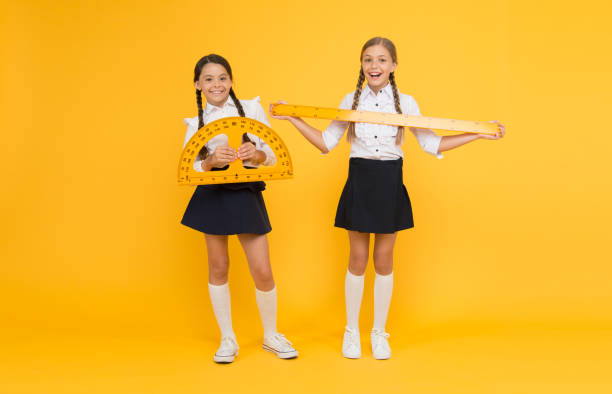 Explore world with math. Discover mathematics patterns. Mathematical theory combining algebraic and geometric methods. School students study geometry. Pupil school girls big rulers. School knowledge stock photo