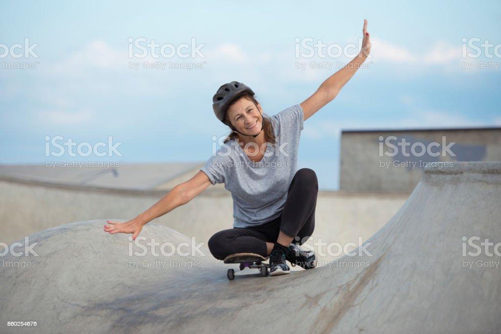 Explore young at heart. Senior woman skateboarding. stock photo