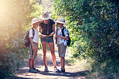 Kids playing safari exploration trip. Brothers and sister walking through difficult path in the wilderness. Kids are reading ancient treasure map.\nSunny summer day.\nNikon D850