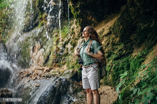 One woman, lady explorer and biologist standing in nature by waterfall alone.