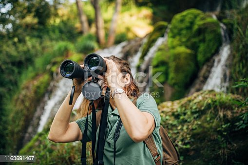 One woman, lady explorer and biologist standing in nature by waterfall alone, using binoculars.