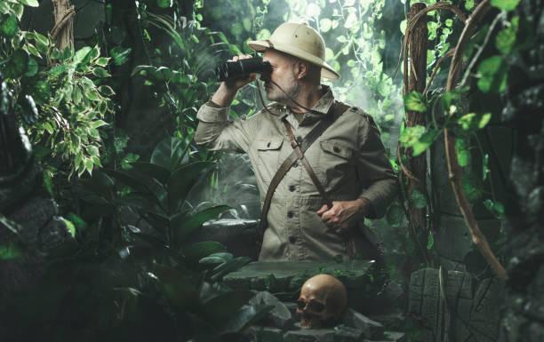 Explorer with binoculars in the jungle stock photo