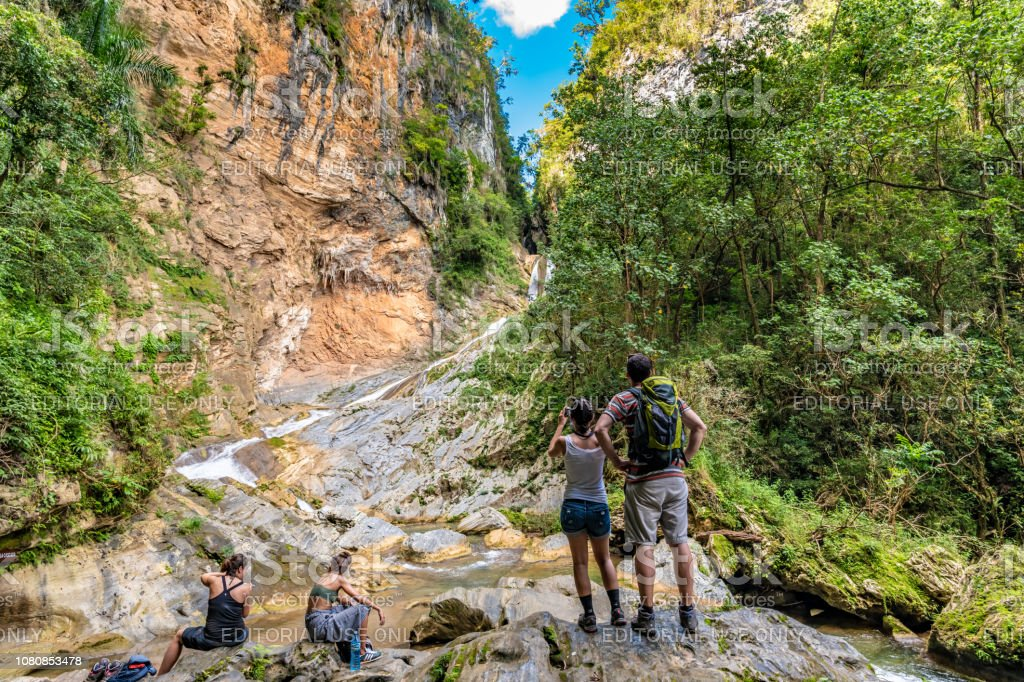 Explorers at a waterfall in the Topes de Collantes nature reserve in the Escambray Mountains stock photo