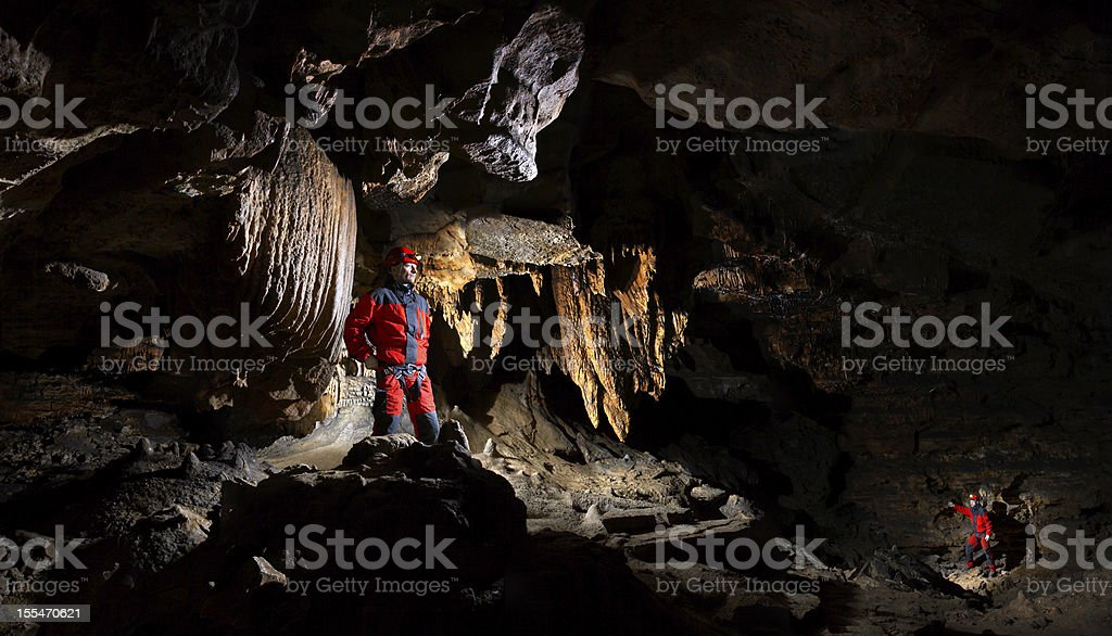 Explorers venturing into hallow cave stock photo