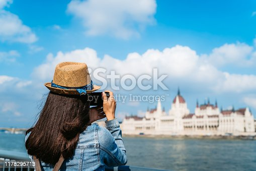 Young woman is standing on the riverbank of the Danube river taking a photo of Hungarian Parliament Building in Budapest, Hungary.